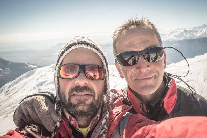 两位登山家Selfie在山上面的在冬天 图库摄影