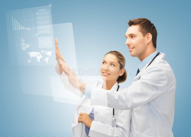 两位医生与虚屏一起使用 库存图片