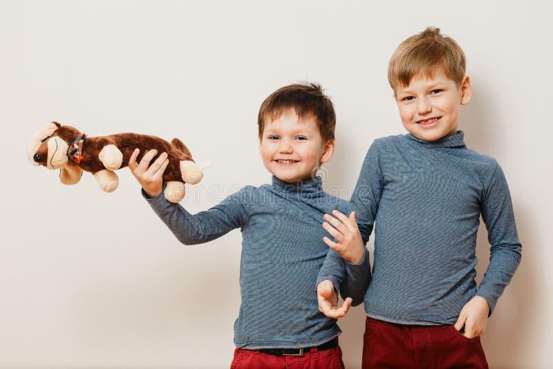 两使用与在白色背景的一个软的玩具的同样镶边高领衫的快乐的兄弟 免版税图库摄影