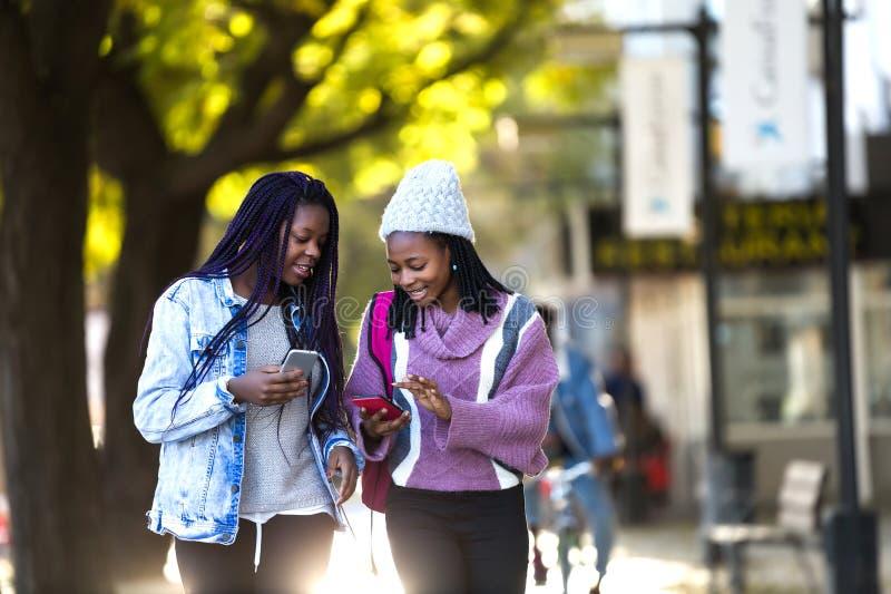 两使用手机的美丽的少妇在街道 免版税库存照片