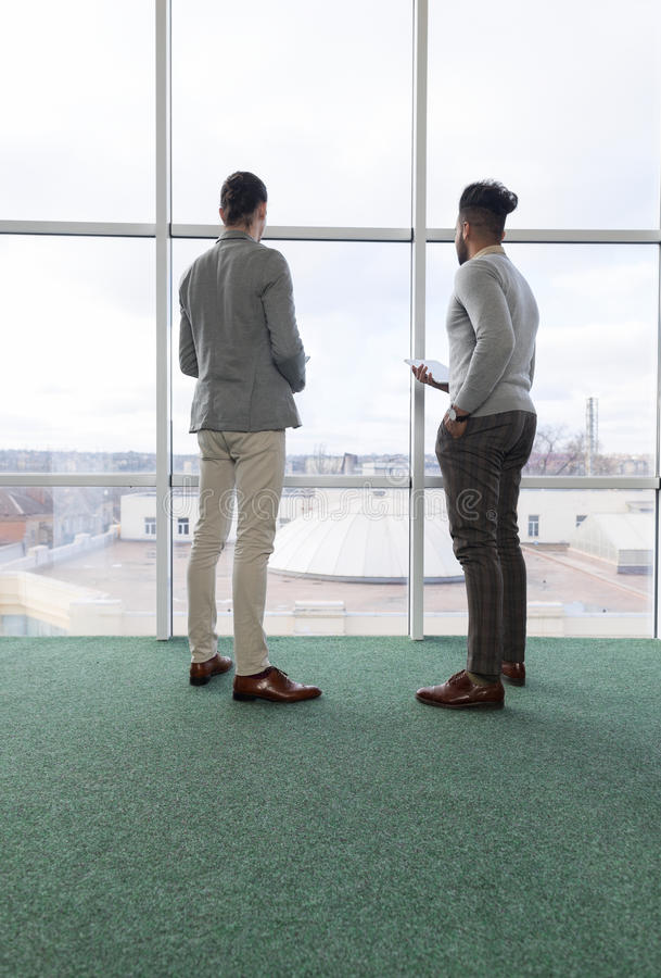 两使用片剂计算机Coworking中心企业队工友的商人在前面大全景窗口里站立 免版税库存照片