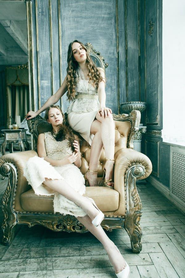 两俏丽的双一起豪华房子内部的姐妹白肤金发的卷曲发型女孩,富有的年轻人概念 免版税库存图片