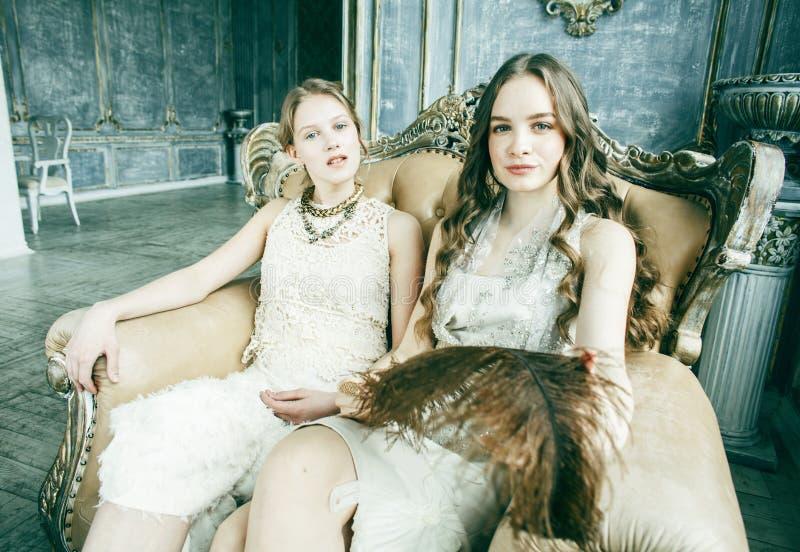 两俏丽的双一起豪华房子内部的姐妹白肤金发的卷曲发型女孩,富有的年轻人概念 图库摄影
