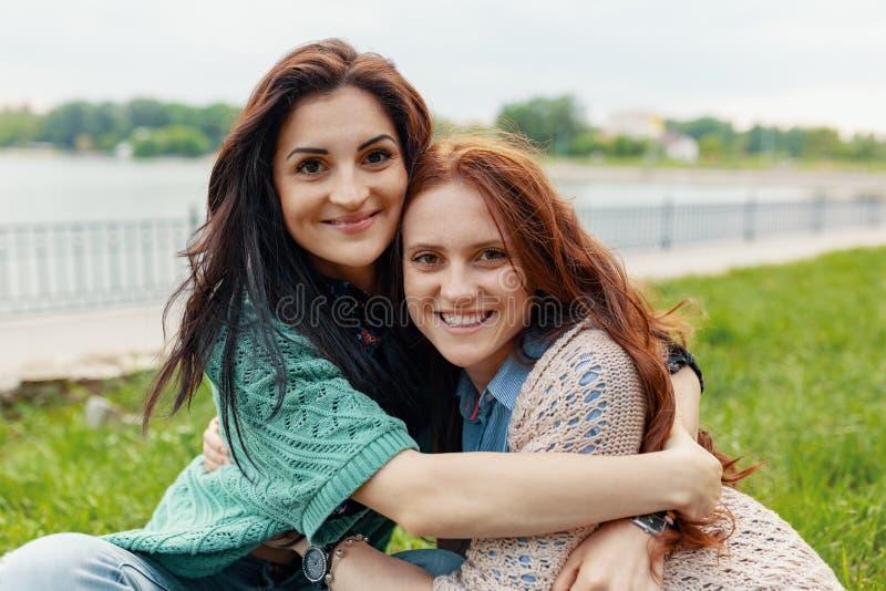 两俏丽的女友微笑的拥抱和有乐趣画象  免版税库存图片