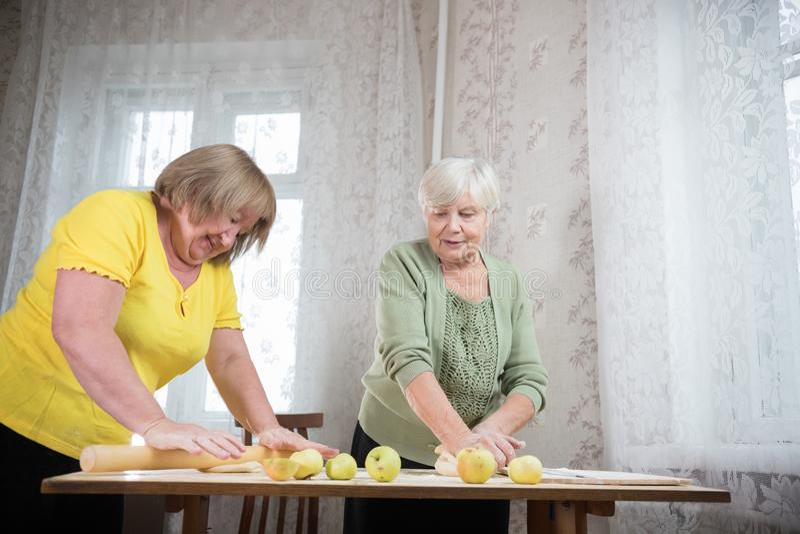 两做小的饼的年长妇女 面团揉 库存照片