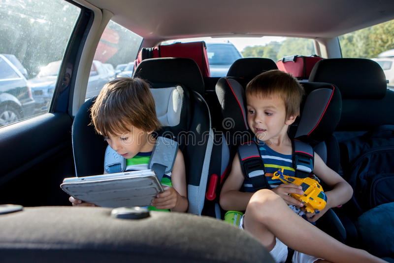 两儿童汽车座椅的男孩,旅行乘汽车和使用与 免版税库存图片