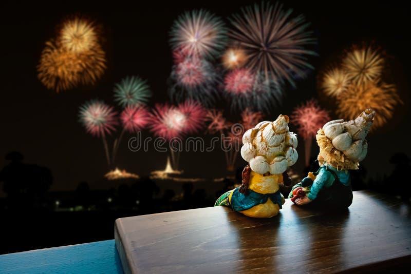 两儿童玩具坐的和观看的烟花 免版税库存图片