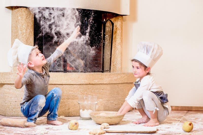 两兄弟姐妹-男孩和女孩-厨师在壁炉附近的` s帽子的坐厨房地板弄脏用面粉,使用用食物 免版税库存图片