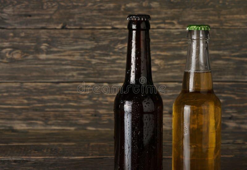 两冒汗,冷的瓶在黑暗的木背景的啤酒 免版税库存图片