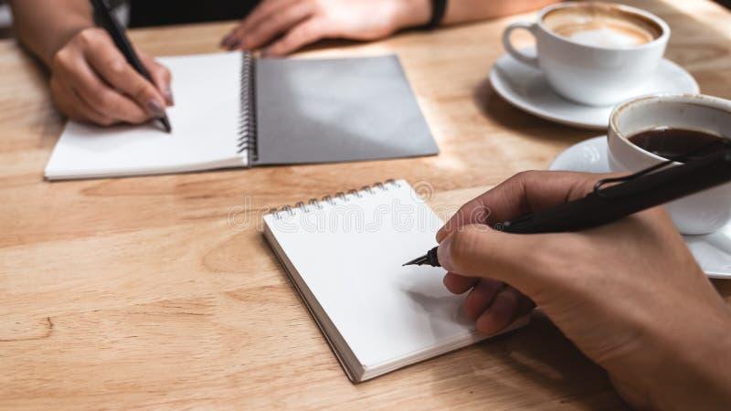 两写下在有咖啡杯的一个白色空白的笔记本的商人在木桌上在办公室 免版税库存图片