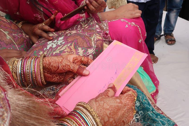 两印地安与礼物的新娘的手有无刺指甲花mehndi的和桃红色礼服和信封 免版税库存照片