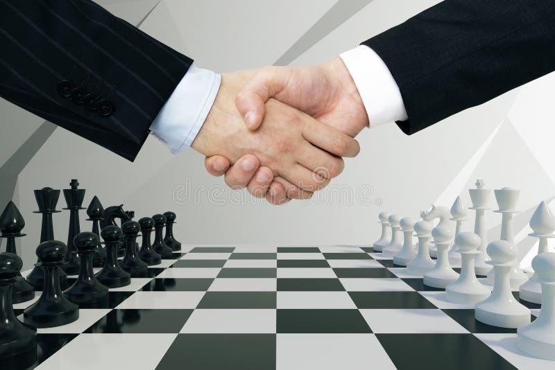 两只商人手与在棋背景握手 免版税库存图片
