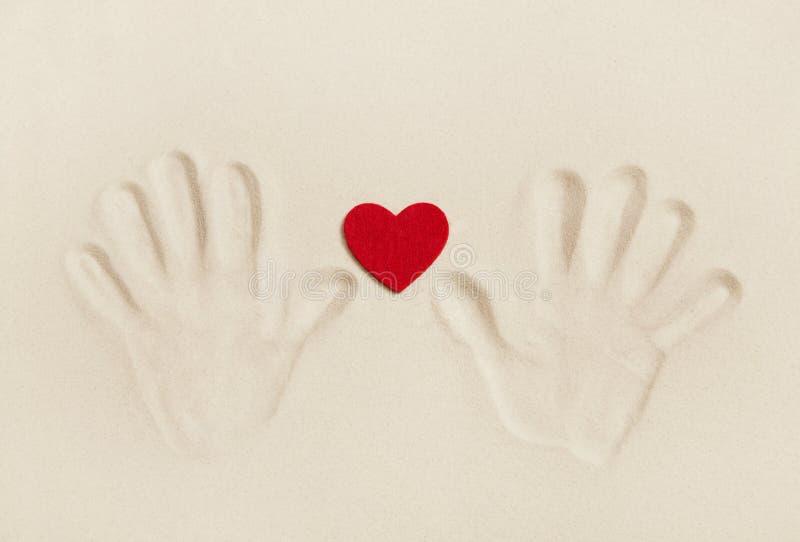两只手在与红色心脏的沙子打印 标志概念为 免版税库存图片