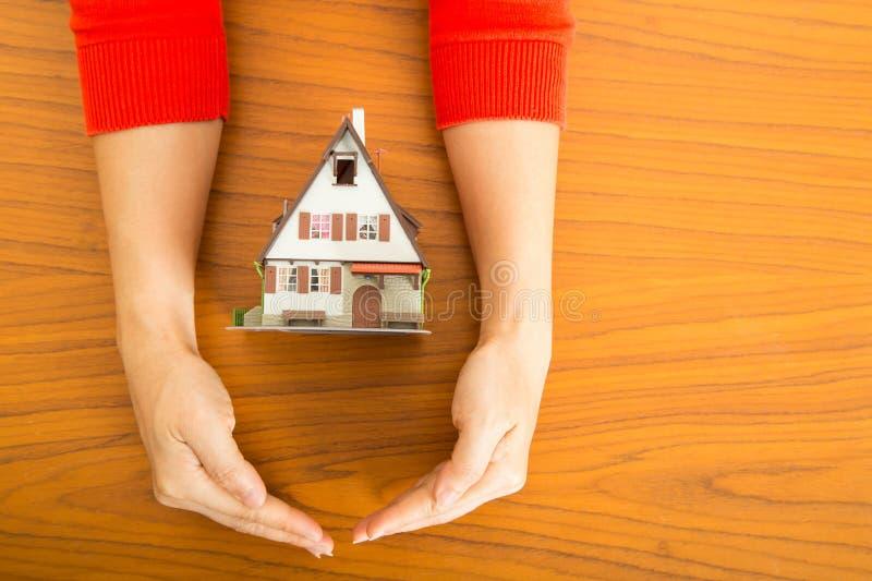 两只手妇女盖子有房地产概念的模型房子 免版税库存照片