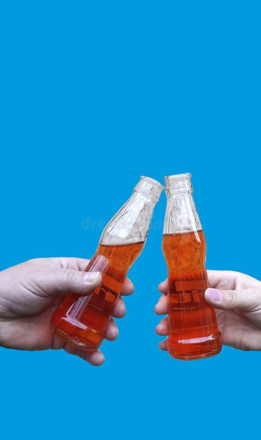 两只手拿着饮料和做多士的,使叮当响的瓶用柠檬水或啤酒,被隔绝在蓝色背景 免版税库存照片