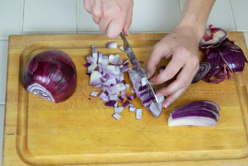两只手接近把在切板的红洋葱切成小方块 免版税库存图片