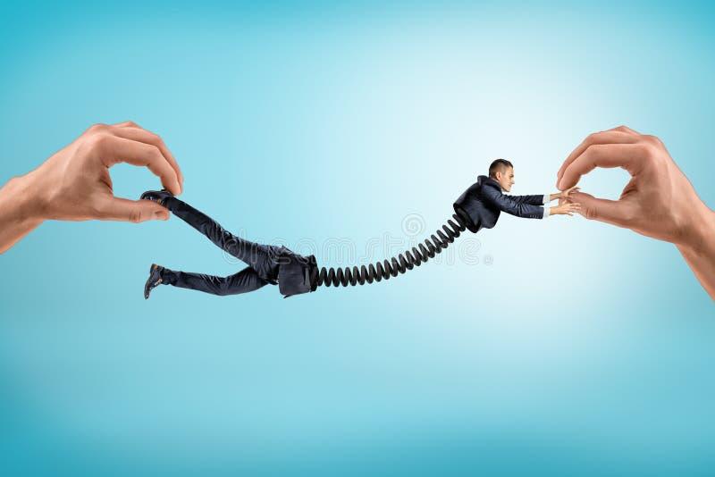 两只手特写镜头在用缆绳导线连接的两部分中的举行一点商人分裂在腰部 免版税库存照片