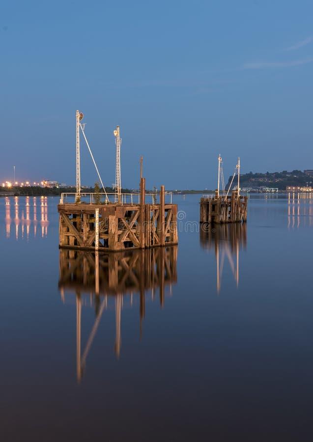 两只木小船跳船的,在一个港口中间,在晚上,反射在非常镇静水中 库存图片