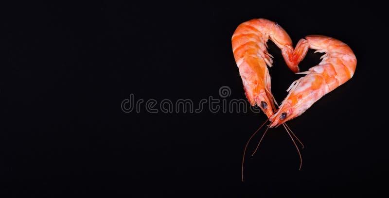 两只虾在黑背景中的形成心脏 免版税图库摄影