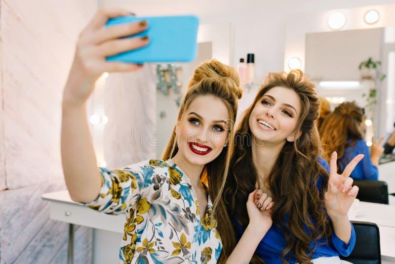 两可爱的微笑的年轻女人获得乐趣,做selfie在电话在美发师沙龙 微笑,表达阳 库存图片