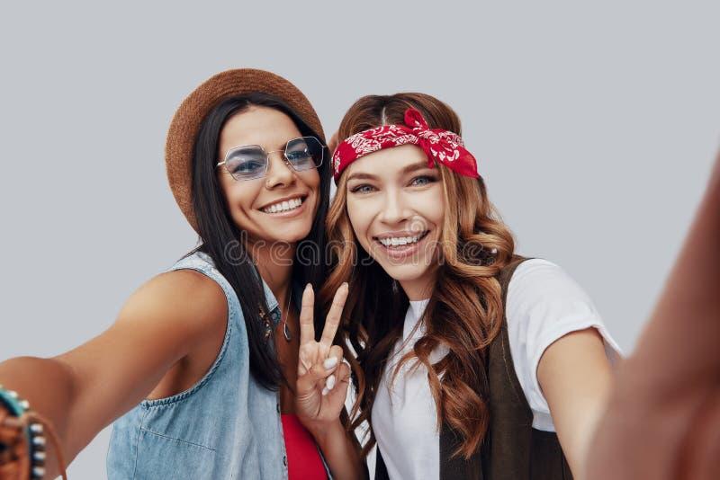 两可爱的时髦的年轻女人自画象  免版税库存图片