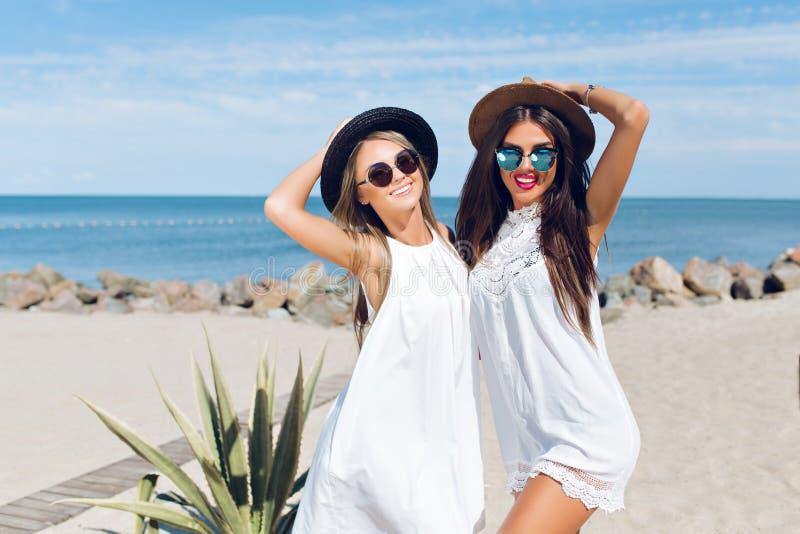 两可爱的浅黑肤色的男人和白肤金发的女孩有长发的在海滩站立在海附近 他们戴帽子,太阳镜 免版税图库摄影