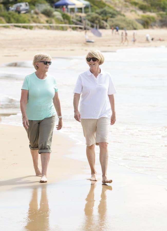 两可爱资深成熟他们的60s的退休的妇女获得乐趣一起享受愉快走在海滩微笑的嬉戏 免版税库存照片