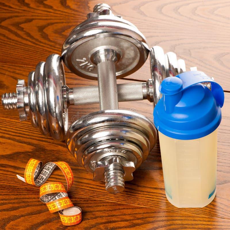 两台哑铃、米磁带和塑料蛋白质振动器在木头 免版税库存照片