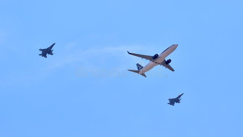 两台喷气式歼击机围拢的Tarom飞机在飞行表演期间 图库摄影