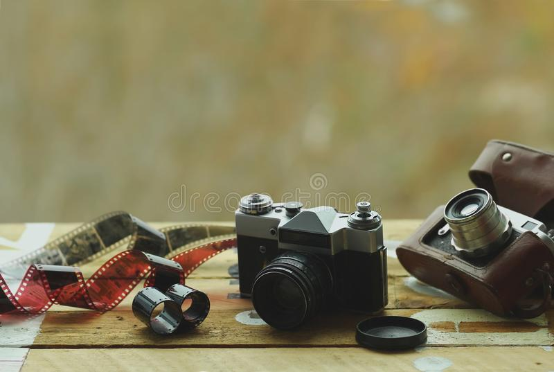 两台守旧派葡萄酒照片照相机和疏散影片在浅褐色的桌上 一在棕色减速火箭的皮革案件持有人 蠢材 免版税库存照片