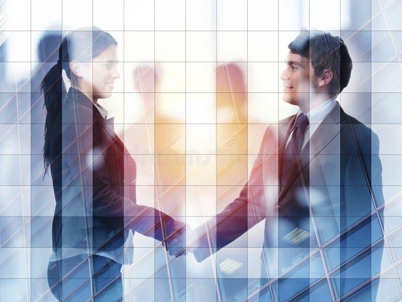 两合作和配合的办公室概念的买卖人握手  两次曝光 免版税库存图片