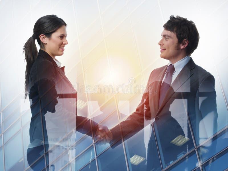 两合作和配合的办公室概念的买卖人握手  两次曝光 库存图片
