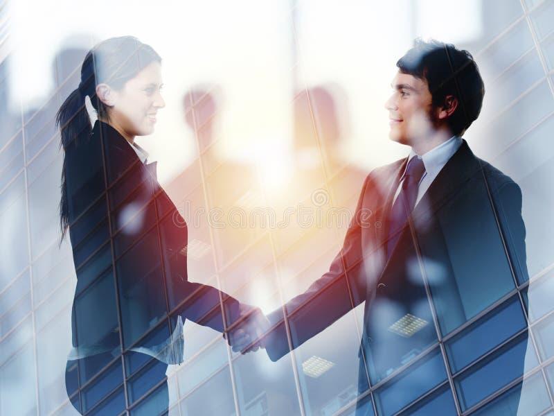 两合作和配合的办公室概念的买卖人握手  两次曝光 免版税库存照片