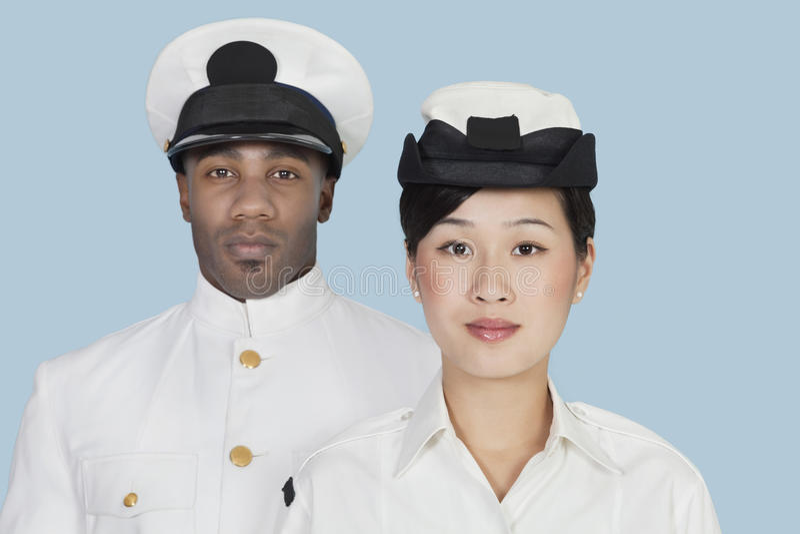 两名不同种族的美国海军官员画象在浅兰的背景的 库存照片