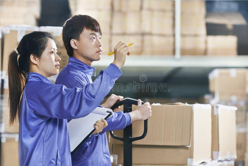 两名中国工作者在仓库里 免版税库存图片