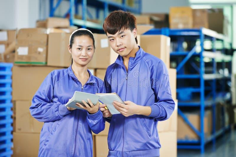 两名中国工作者在仓库里 免版税库存照片