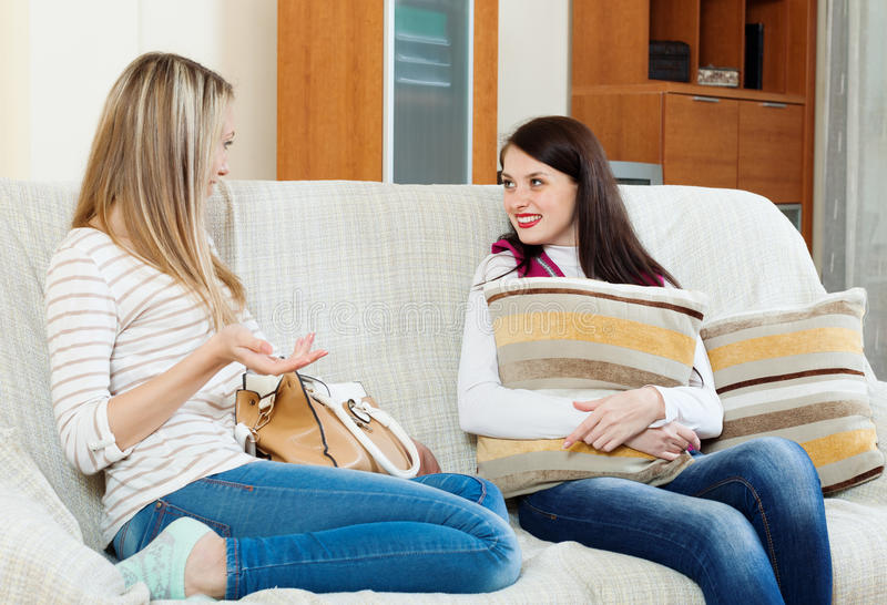 两名偶然妇女说闲话在沙发 库存图片
