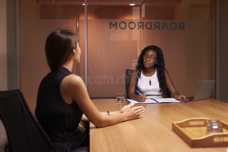 两名公司女实业家在一次晚上会议上在办公室 免版税库存图片