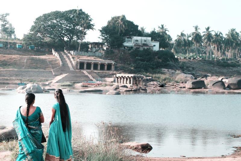 两名印度妇女看河的城市有他们的后面的对在湖的照相机 免版税库存图片