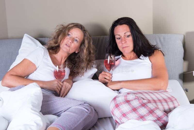 两名可爱的妇女喝一杯在床 免版税库存照片