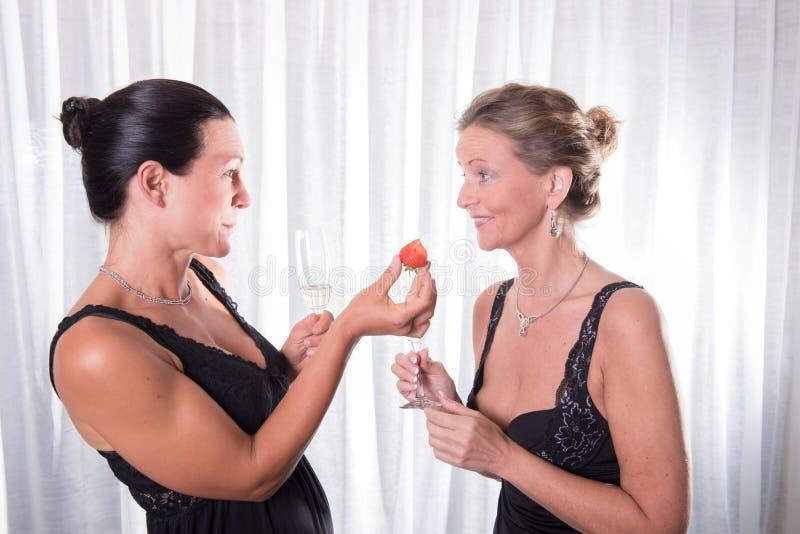 两名可爱的妇女-一个为她的朋友提供草莓 免版税库存图片