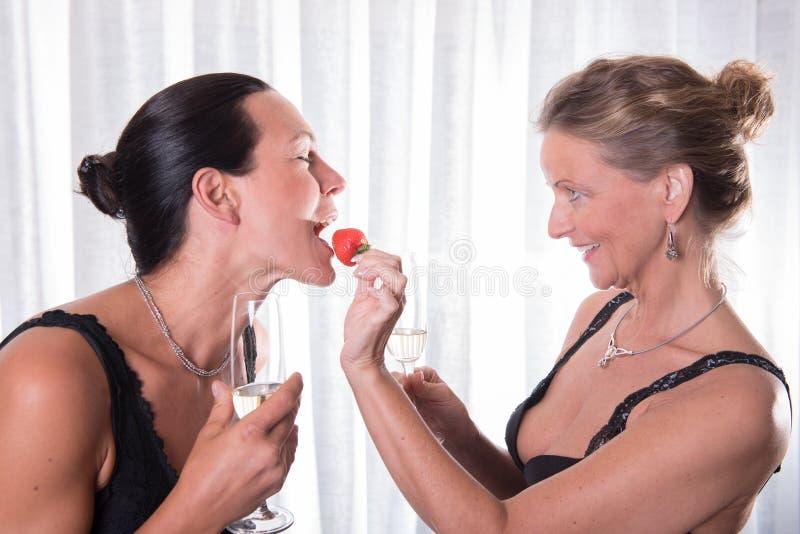 两名可爱的妇女-一个哺养其他用草莓 免版税库存照片