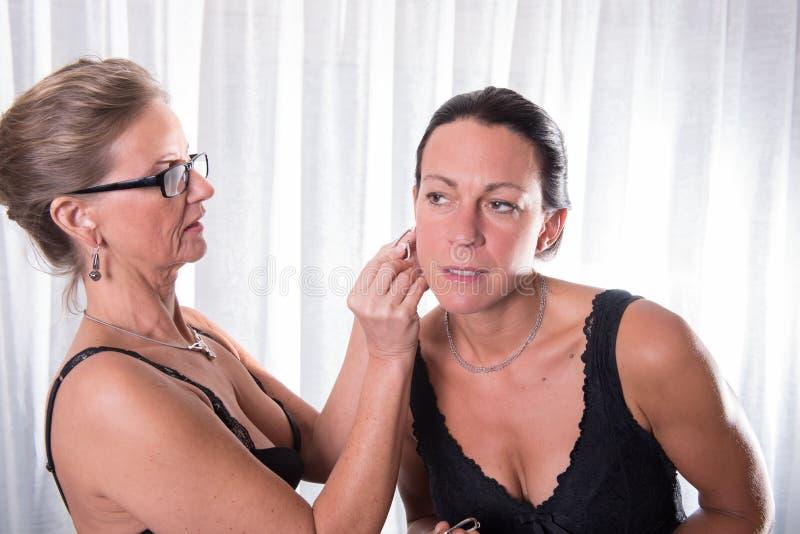两名可爱的妇女-一个投入其他她的耳环  免版税库存照片