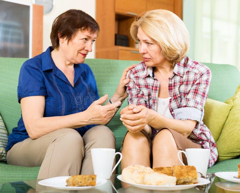 两名哀伤的年迈的妇女谈话在长沙发 免版税库存照片