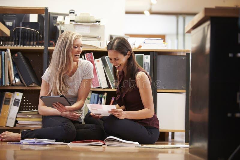 两名女实业家坐与数字式片剂的办公室地板 免版税图库摄影