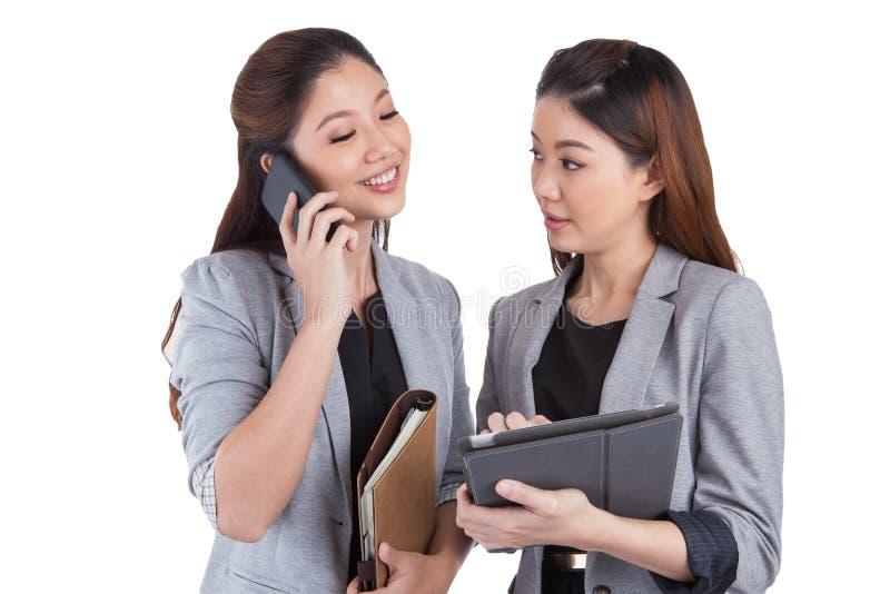 两名女实业家用途手机和片剂 库存照片