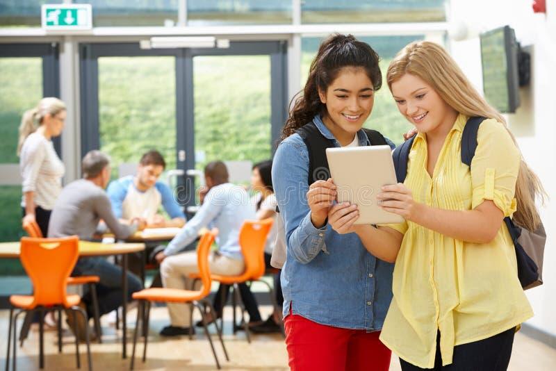 两名女性少年学生在有数字式片剂的教室 免版税库存图片