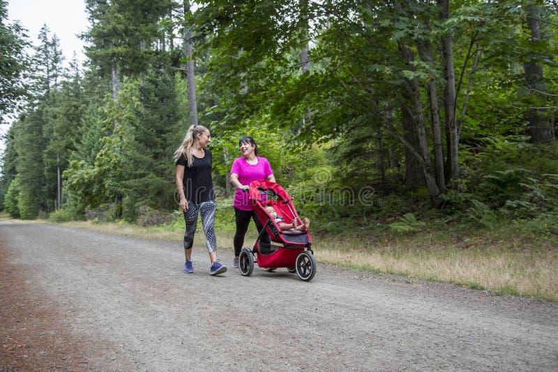 两名妇女一起走和谈话在与婴儿车的一串足迹 图库摄影