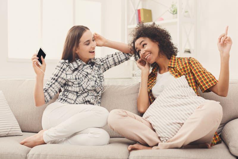 两名妇女听的音乐和分享耳机 库存图片