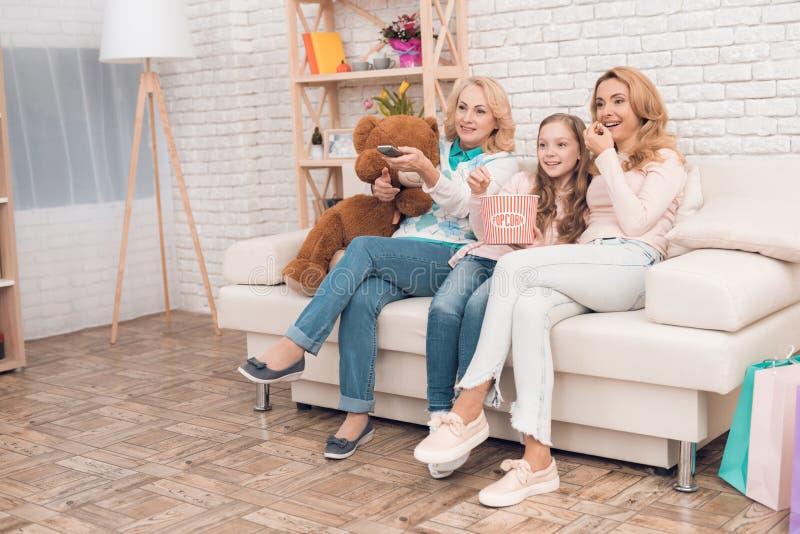 两名妇女和女孩坐长沙发和看着电视 免版税库存照片